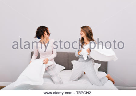 Two pretty pajams girls having pillow fight on bed. They are laughing to each other - Stock Photo