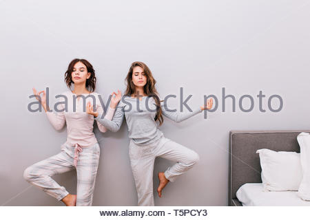 Two young pretty girls in night pajamas on grey wall background. They doing meditation with closed eyes - Stock Photo