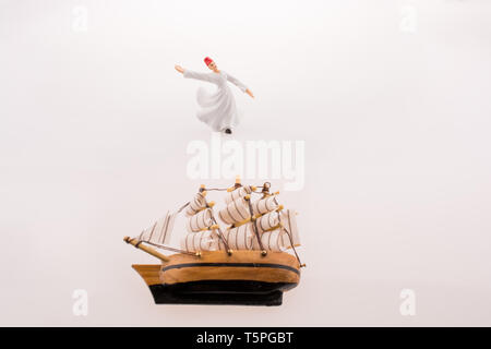 Sufi Dervish near a ship on a white background - Stock Photo