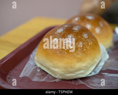 Baked pork bun on tray at small dim sum dining eatery - Stock Photo