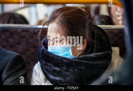 Older Asian woman wearing black fur scarf and surgical pollution mask sitting on a bus train subway - Stock Photo
