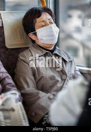 Older Asian woman wearing a tan raincoat and surgical pollution mask sitting on a bus train subway - Stock Photo