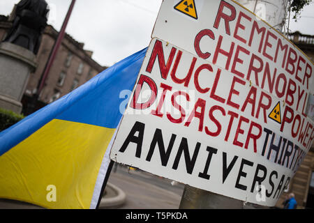 Glasgow, Scotland, 26th April 2019. 78-years old Jim Gillies stands in George Square with his placard remembering the 1986 Chernobyl nuclear disaster in the Ukraine. Today marks the 33rd anniversary of the disaster and Jim Gillies has marked the disaster day, by standing with his placard in the Square ever year since, as well as donating more than £20,000 GBP to a hospital in Ukraine, a country he has now visited approximately 20 times. Credit: jeremy sutton-hibbert/Alamy Live News - Stock Photo