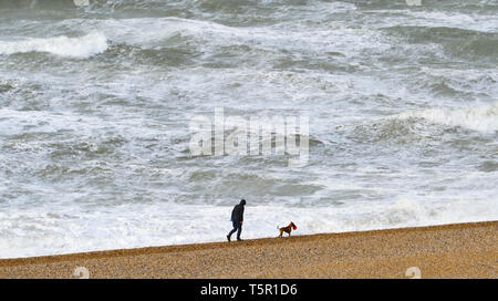 Brighton, UK. 27th Apr, 2019. A lone dog walker on Brighton beach as Storm Hannah hits Britain this morning with strong winds forecast to affect parts of the country Credit: Simon Dack/Alamy Live News - Stock Photo