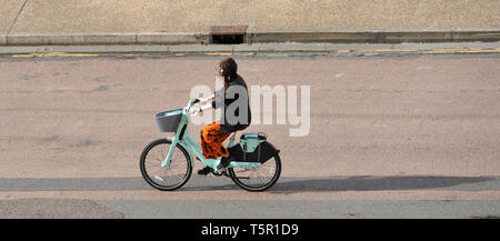 Brighton, UK. 27th Apr, 2019. A woman on a hirebicycle gets blown along Brighton seafront as Storm Hannah hits Britain this morning Credit: Simon Dack/Alamy Live News - Stock Photo