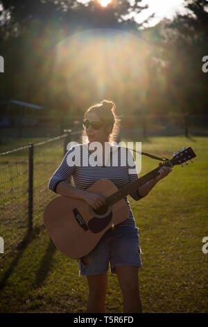 Young Woman Playing Guitar in a Field - Stock Photo
