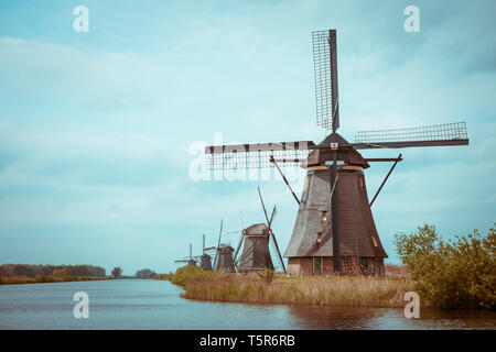 Traditional Dutch windmills on a canal bank in Nethelands vintage color toned - Stock Photo