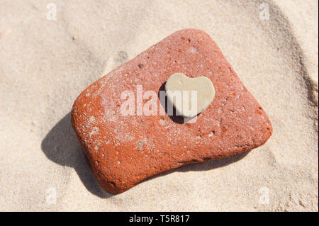 Heart shaped stone on a sandy beach - Stock Photo