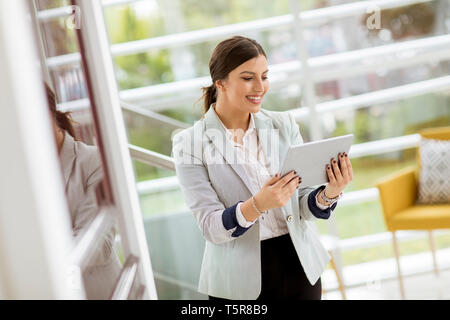 Portrait of attractive young business woman smiling confidently and working online with a digital tablet while standing in the modern office - Stock Photo