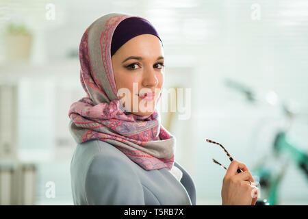 Beautiful stylish woman in hijab and eyeglasses, sitting at desk with laptop in office. Portrait of confident muslim businesswoman. Modern office with - Stock Photo