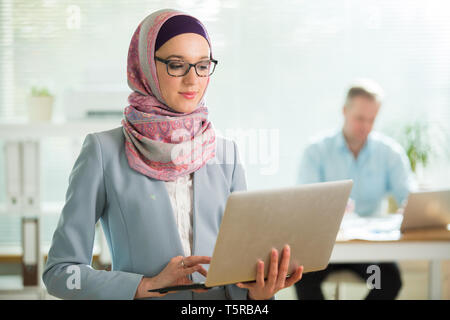 Beautiful stylish woman in hijab and eyeglasses standing in office, holding laptop. Portrait of confident muslim businesswoman. Modern office with big - Stock Photo