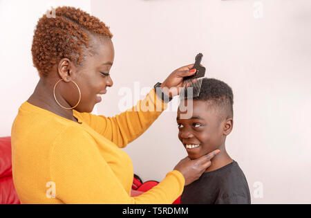 Andover, Hampshire, England, UK. April 2019. Nine year old boy with curly hair with his mother using a wide tooth afro comb for his hair.