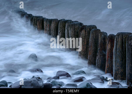 A row of wooden groynes on the beach at Porlock, Somerset, as the incoming tide washes over them. - Stock Photo