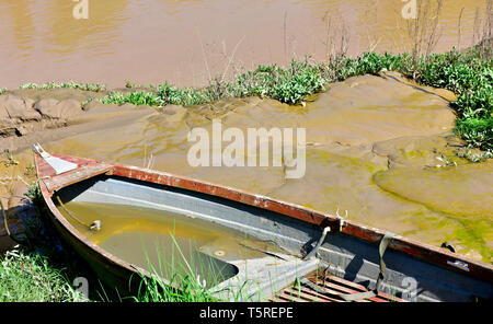 Small boat partly filled with water on mud bank of river - Stock Photo