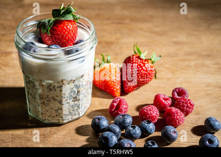 Jam jar overnight oats and yoghurt in a glass jam jar on rustic wooden bench with fresh strawberries, raspberries and blueberries - Stock Photo