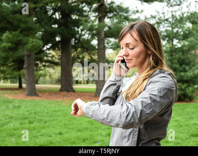 Young woman on cell, mobile phone looking at watch in city park on overcast day, smiling, with green grass, trees background - Stock Photo