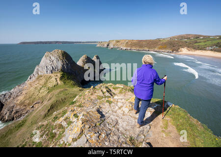 Walker standing above the Three Cliffs Bay at high tide, Gower Peninsula, Swansea, West Glamorgan, Wales, United Kingdom, Europe - Stock Photo