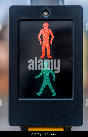 The classic design of the pedestrian crossing showing both the red and green man illuminated. - Stock Photo