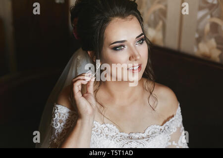 Beautiful model plus size in a fashionable wedding dress and with stylish wedding hairstyle adjusting her earring before the wedding ceremony - Stock Photo