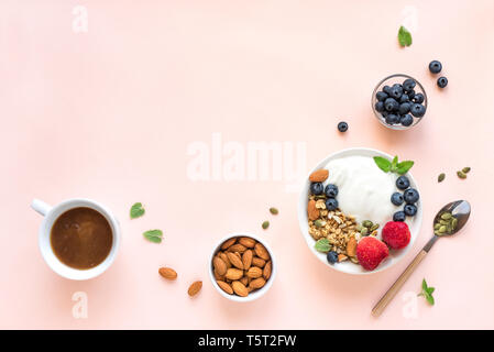 Greek yogurt with homemade granola and berries for healthy breakfast on pink pastel background, top view, copy space. - Stock Photo