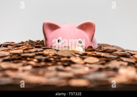 Pink piggy bank drowning in ocean of copper pennies. - Stock Photo