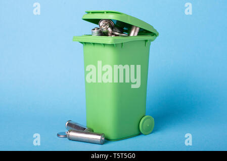 Dustbin on a blue background. Batteries, batteries. Waste recycling. Ecological concept. - Stock Photo