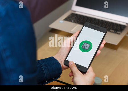 SAN FRANCISCO, US - 22 April 2019: Close up to female hands holding smartphone using Google Android Things Toolkit application, San Francisco, Califor - Stock Photo