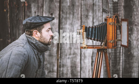Selfie of old fashioned man on large format camera. Idea - self-portrait - Stock Photo