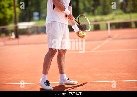 Lower body of tennis players preparing to serve on court - Stock Photo