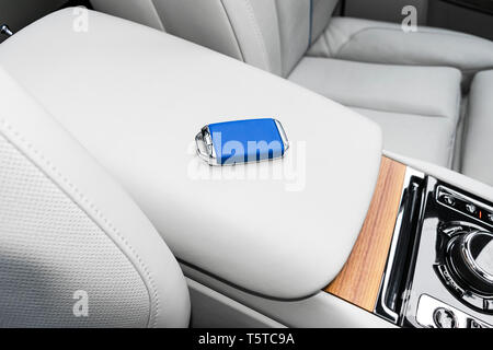 Closeup inside vehicle of wireless blue leather key ignition on natural wood panel. Wireless start engine key. Car key remote isolated. Modern Car key - Stock Photo