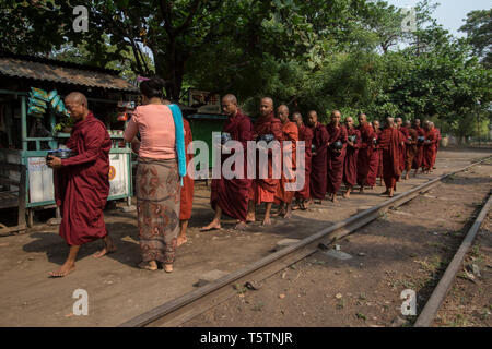 Buddhist monks receiving alms by a railway track in Thazi, Shan State, Myanmar. - Stock Photo