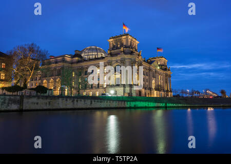 Illuminated German parliament building Reichstag and its glass dome by the Spree River in Berlin, Germany, at dusk. - Stock Photo