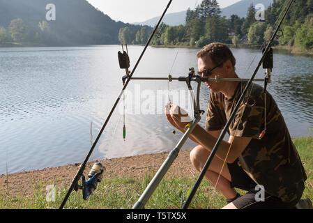 Fishing adventures, carp fishing. Angler is preparing the equipment - Stock Photo