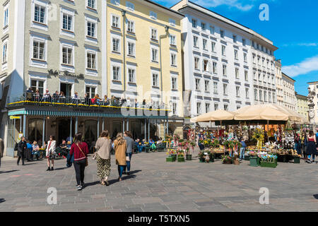 Salzburg Austria, view of market stalls and people sitting at a cafe terrace in Alter Markt in the Old Town quarter (Altstadt) of Salzburg, Austria. - Stock Photo