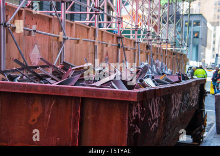 Rusty dumpster full of metal scrap at construction site on a city street with large buildings in the background. There is scaffolding and a plywood pr - Stock Photo