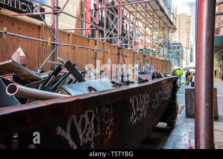 New York, NY - April 3, 2019: Rusty dumpster full of metal scrap at construction site on a city street with large buildings and scaffolding in the bac - Stock Photo
