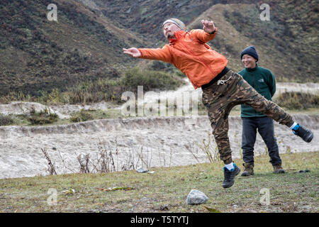 Man jumping and throwing a stone, Dego (Traditional Bhutanese game), Chozo, Lunana Gewog, Gasa District, Bhutan - Stock Photo