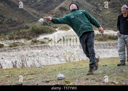 Men playing dego (Traditional Bhutanese game), Chozo, Lunana Gewog, Gasa District, Bhutan - Stock Photo
