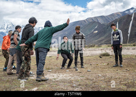 Men playing dego (Traditional Bhutanese game) in Chozo, Lunana Gewog, Gasa District, Bhutan - Stock Photo
