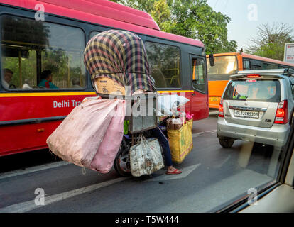 Man on an overladen motorcycle riding through heavy traffic in Delhi Northern India - Stock Photo
