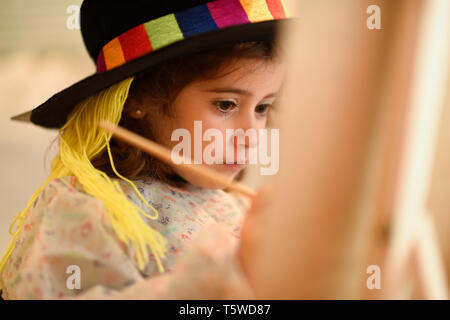 Little girl painting a picture at home - Stock Photo