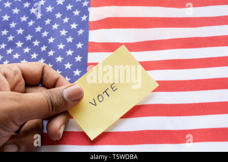 Concept of US election, Vote sticker holding in hand on US flag - Stock Photo