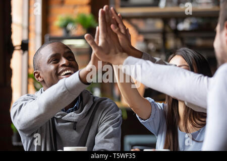 Cheerful different ethnicity friends sitting in cafe giving high five - Stock Photo