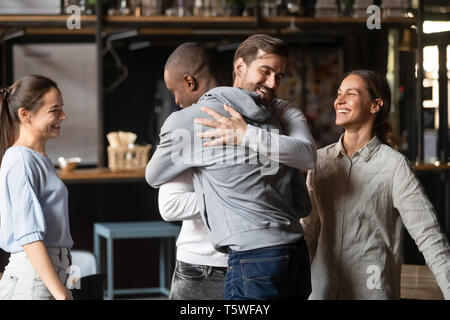 Diverse guys best friends hugging greeting each other at meeting