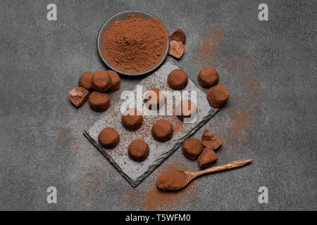 classic chocolate truffles and cocoa powder on dark concrete background - Stock Photo