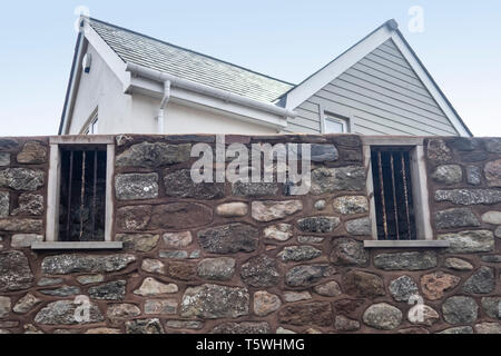 Old barred windows of Sidmouth Jail left in a wall as part of a new housing development. Town jail bars. - Stock Photo
