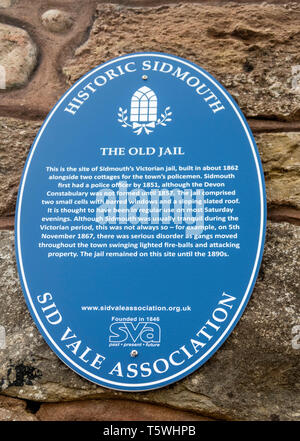 Blue plaque sign telling about the old barred windows of Sidmouth Jail left in a wall as part of a new housing development. Town jail bars. - Stock Photo
