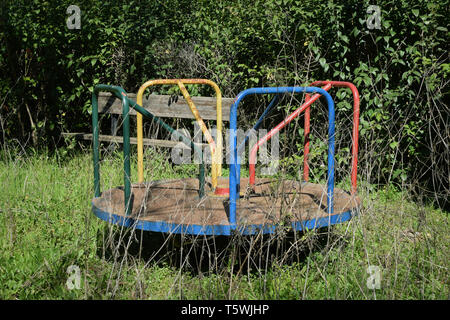 Old rusty playground merry-go-round and overgrown withered plants in abandoned park. - Stock Photo