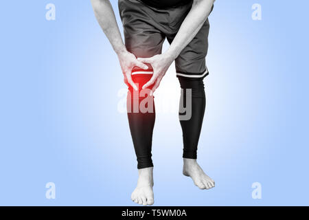 Muscle man holds his injured knee on blue background. Red color is pain. - Stock Photo