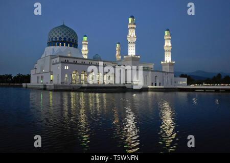 City Mosque on Likas Bay illuminated at dusk, Kota Kinabalu, Sabah (Borneo), Malaysia - Stock Photo